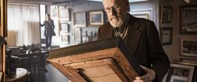 A man looking down at an old wooden picture frame.